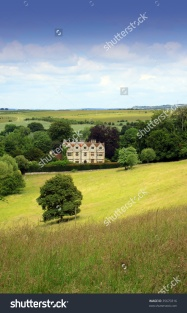 stock-photo-portrait-format-image-of-a-country-manor-looking-across-an-open-rolling-field-to-the-foreground-35670316